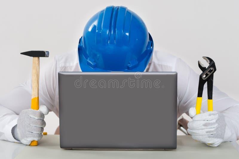 Pinces de Holding Hammer And de technicien avec l'ordinateur portable photos stock