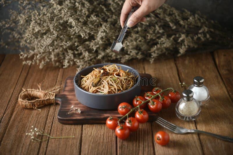 Pinces de nourriture en main allant bifurquer lignes de spaghetti de plat et de plat en bois pour servir avec l'environnement fai photo libre de droits