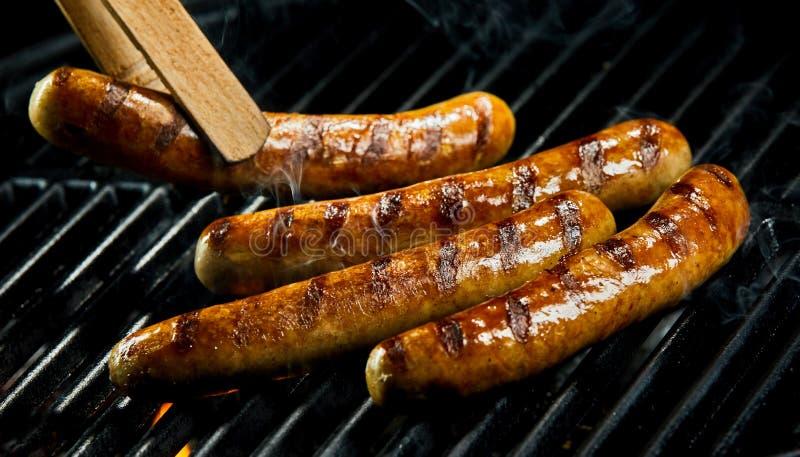 Pinces en bois tournant des saucisses sur le gril de barbecue photographie stock libre de droits
