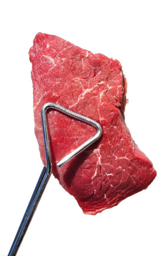 Pinces retenant le bifteck d'aloyau cru de dessus d'échine de boeuf photographie stock libre de droits