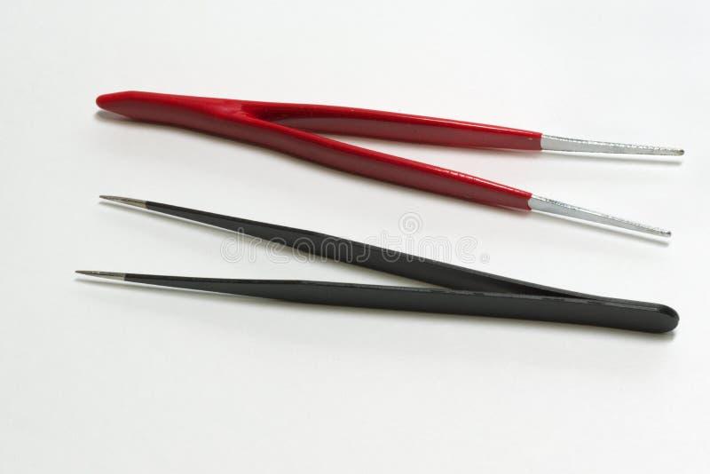 Pincett för elektronikreparationen, raksträcka, rött och svart royaltyfri bild