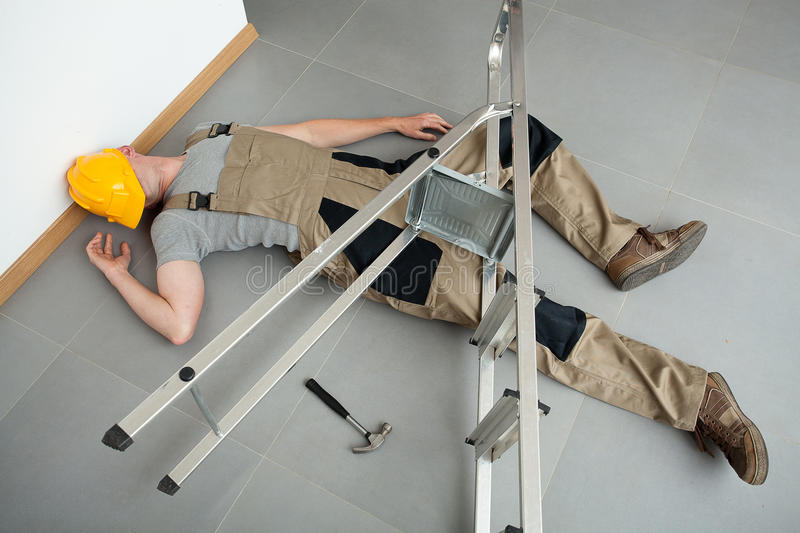 Pinched by a ladder. A worker pinched by a ladder which has fallen on him royalty free stock image