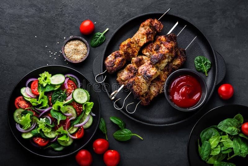 Pinchos asados a la parrilla de la carne, kebab y ensalada vegetal sana del tomate, del pepino, de la cebolla, de la espinaca, de imagenes de archivo