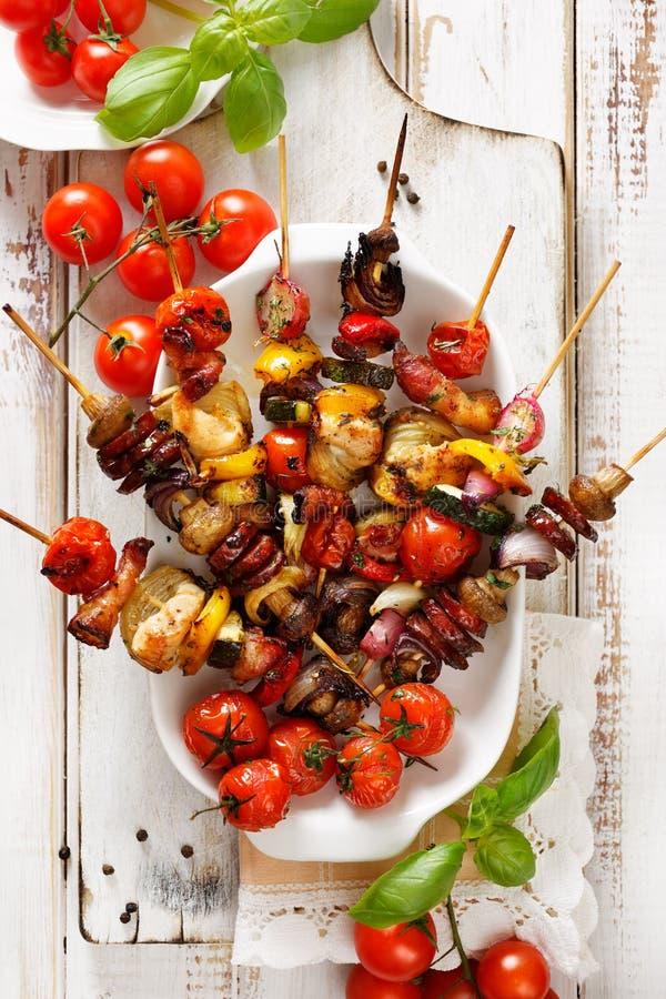 Pinchos asados a la parrilla de verduras y de la carne en un adobo de la hierba en la placa blanca fotos de archivo libres de regalías