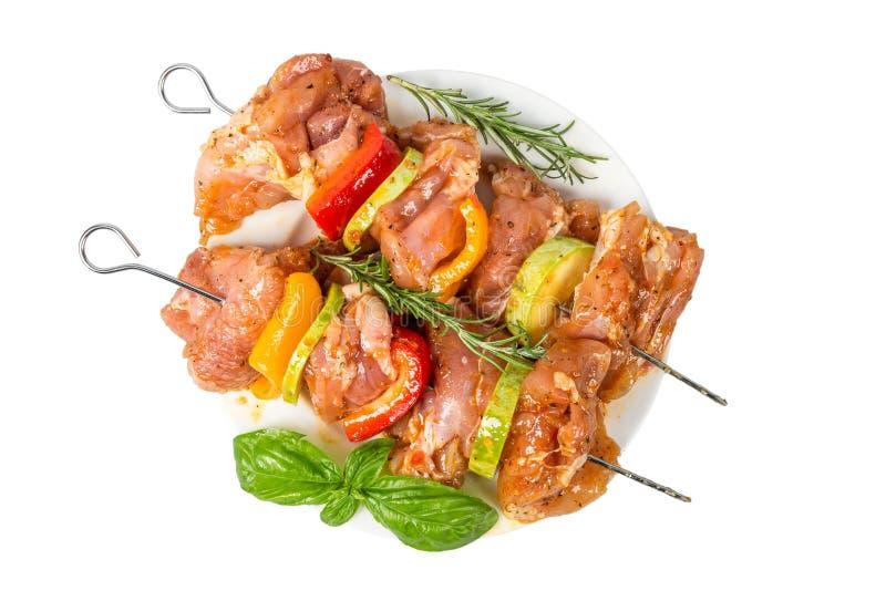 Pinchos de la carne cruda y de las verduras en adobo en la placa aislada en el fondo blanco Visi?n superior imagen de archivo