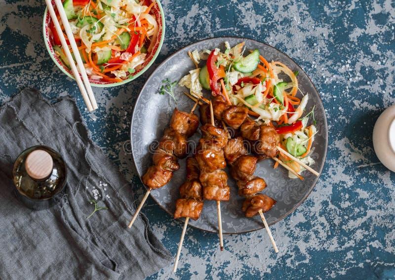 Pinchos del cerdo de Teriyaki y ensalada vegetal adobada Almuerzo asiático del estilo imagen de archivo libre de regalías