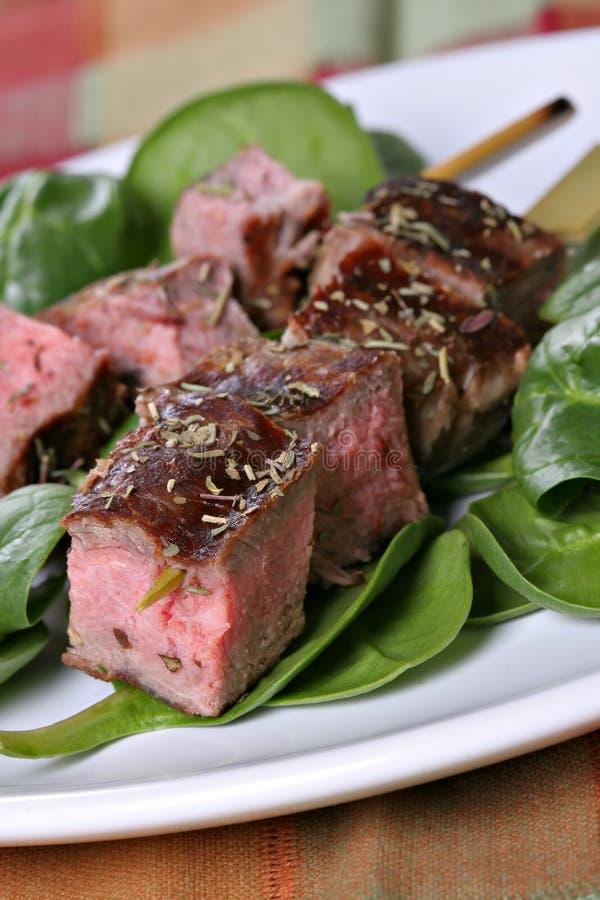 Pinchos del filete de carne de vaca sobre espinaca fotografía de archivo libre de regalías