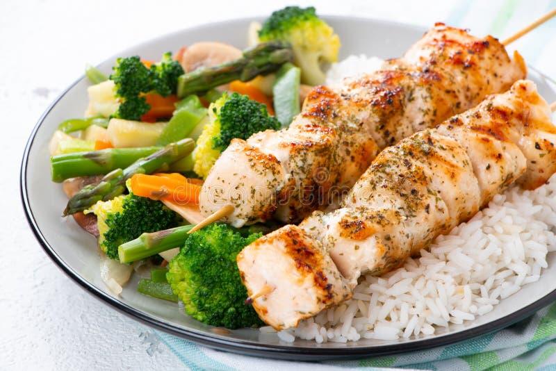 Pinchos del pollo con las verduras cocidas al vapor y el arroz largo fotografía de archivo