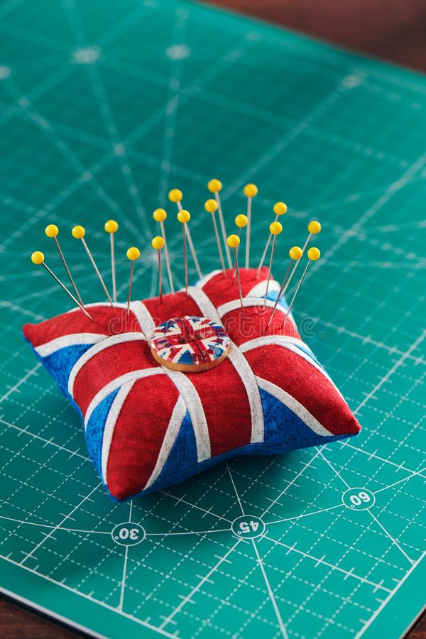 Pincushion jak Union Jack na zielonej rzemiosło macie, żółta piłki głowa szy szpilki zdjęcia stock