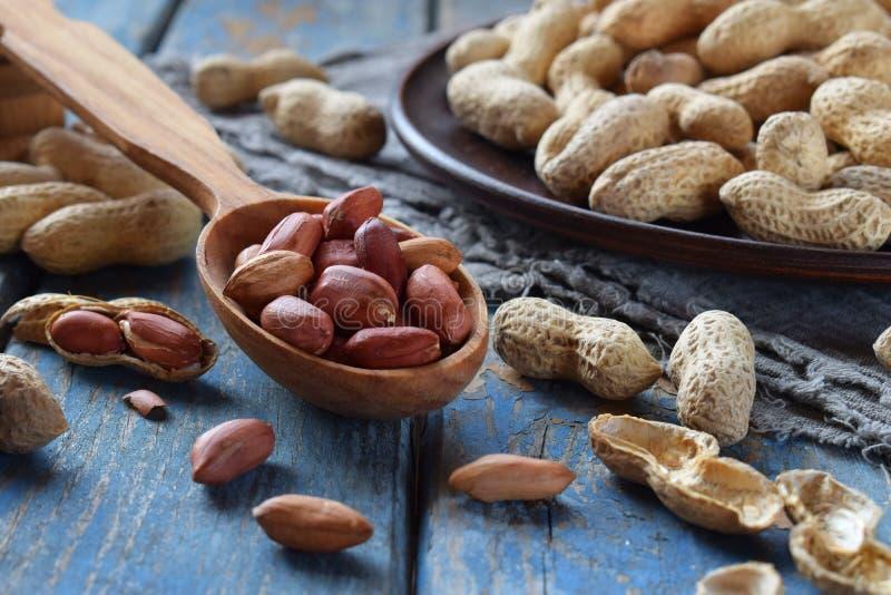Pinda's in notedop en gepelde pinda op houten achtergrond Gezonde en dieetvoeding Ruw voedsel stock foto's