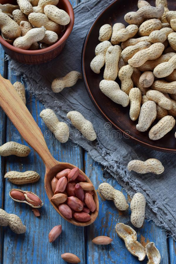 Pinda's in notedop en gepelde pinda op houten achtergrond Gezonde en dieetvoeding Ruw voedsel royalty-vrije stock afbeelding