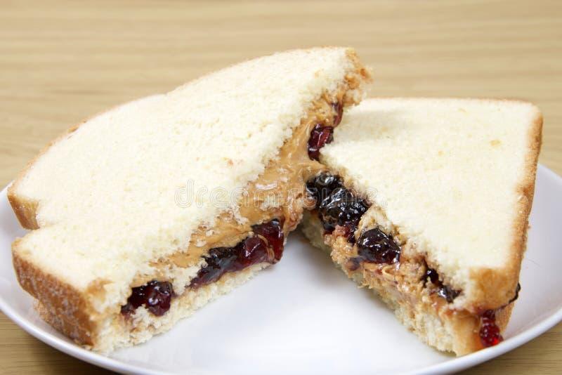 Pindakaas en Jelly Sandwich-besnoeiing in half gediend op plaat stock fotografie