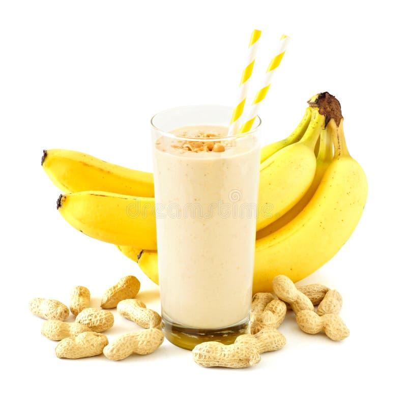 Pindakaasbanaan smoothie met verspreide ingrediënten over wit stock afbeeldingen