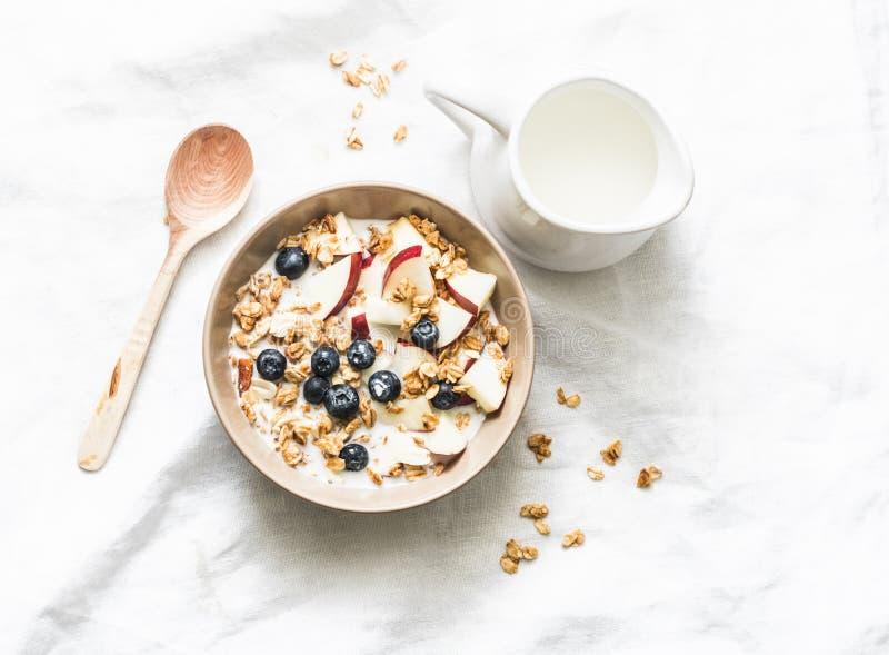 Pindakaasgranola met melk, appelen en bosbessen - gezonde energieontbijt of snack op een lichte achtergrond, hoogste mening royalty-vrije stock foto's