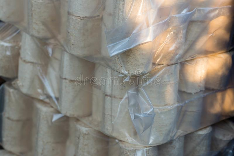 Pine and beech wood briquette in plastic bags for the cold season. Close up shot royalty free stock photos
