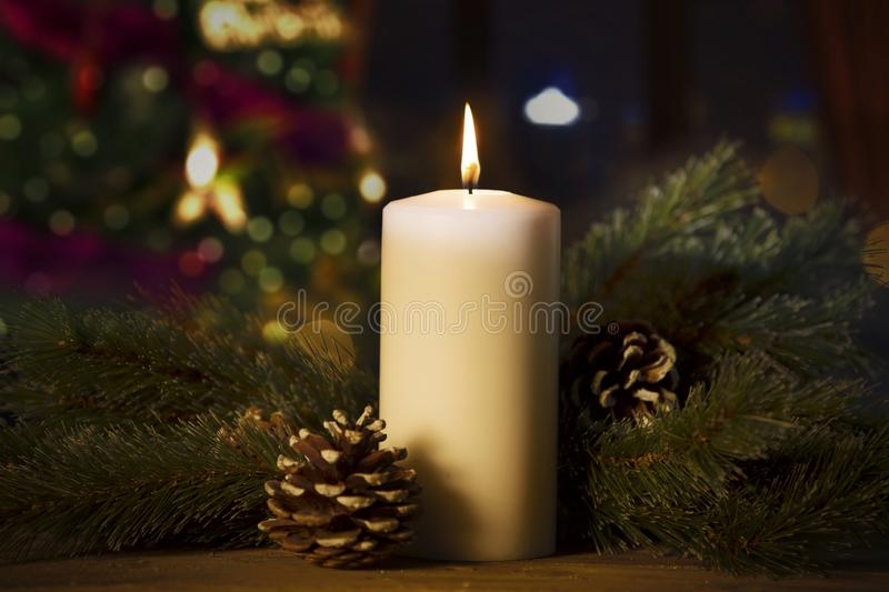 Pine branches with burning candle on the table. Closeup of pine branches and pine cones with a burning candle on the table royalty free stock image