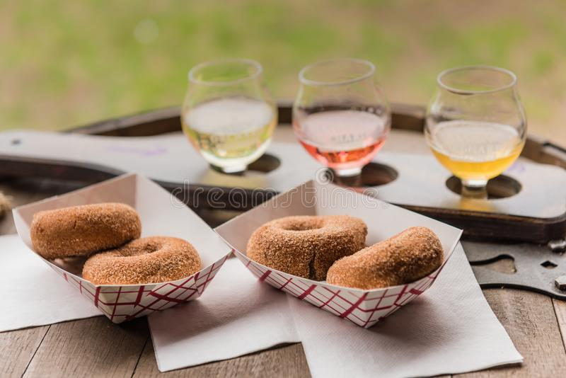 Cider Donuts in Basket with Cider Flight. Pine Bush, NY /USA - June 9, 2018: Cider donut making station at Angry Orchard Cidery royalty free stock image