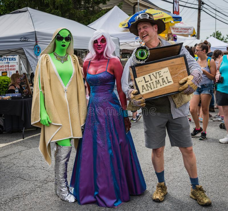 Pine Bush UFO Fair Alien Hunter and Beauties. Pine Bush, NY /USA - June 9, 2018: Man dressed as alien hunter poses with two aliens stock photo