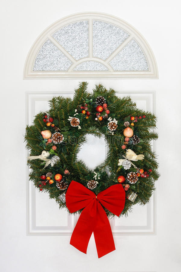 Pine Christmas Wreath With Red Bow Hanging On White Door