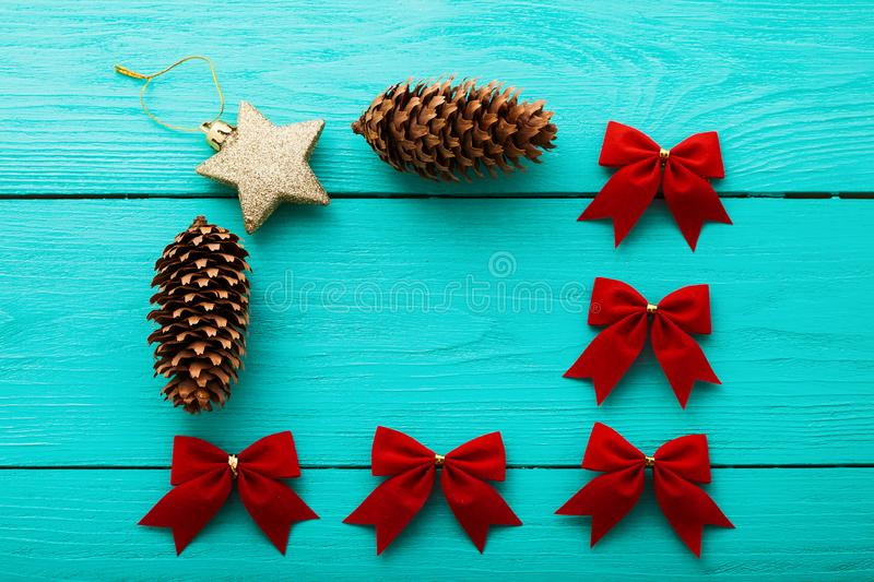 Pine cone and New Year toys. Mock up. Frame of Christmas accessories on blue wooden background. Top view stock photo