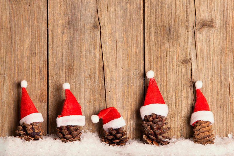 Pine cones with Christmas hats on wooden background. In the snow royalty free stock photography