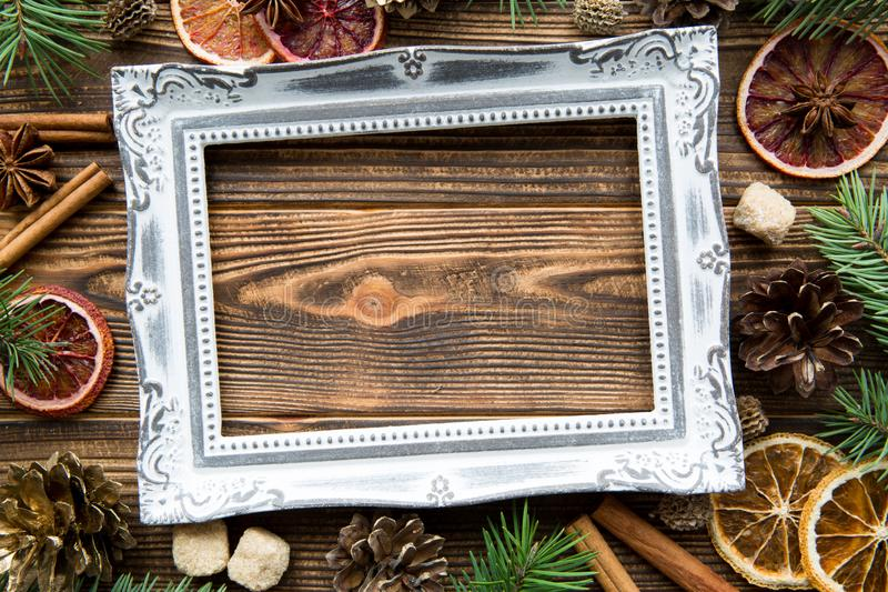 Pine cones, fir tree branches and dried orange slices background. Christmas mood decorations on brown wooden table. Copy space, royalty free stock photo