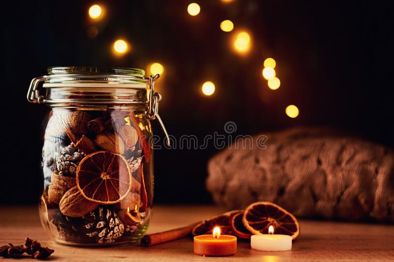 Pine cones in glass jar and fairy lights on a dark background. Festive decorations royalty free stock images