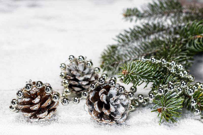 Pine cones and silver pearls on the snow. Pine cones, branch of a fir tree with and silver pearls on the wooden board covered with snow with copy space for text royalty free stock photography