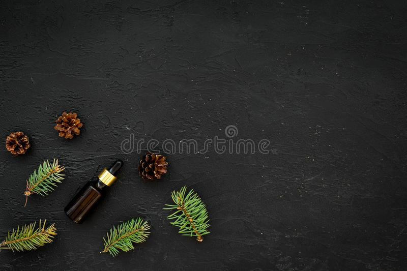 Pine essential oil in bottles on black background top view. Pattern with pine branch and cone copy space royalty free stock photos