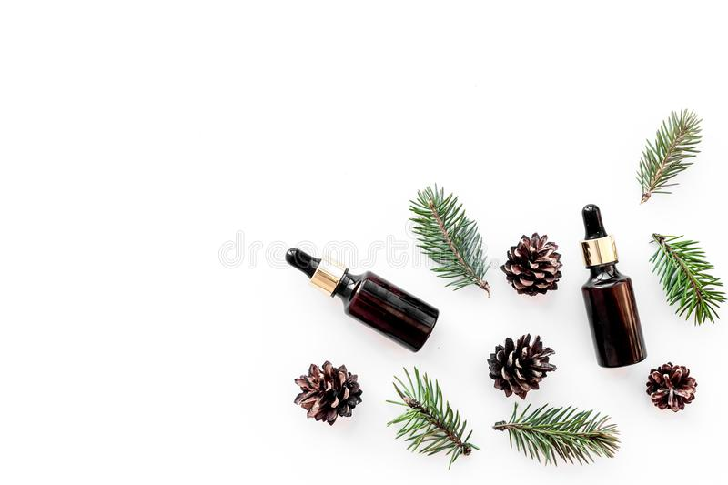 Pine essential oil in bottles on white background top view copy space. Pattern with pine branch and cone royalty free stock photos