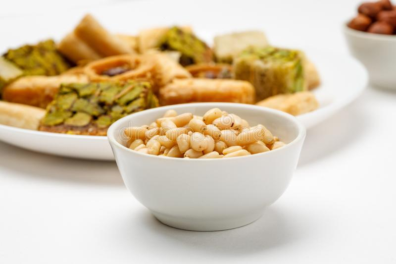 Pine nut in ceramic bowl with traditional oriental sweets in the background, close-up stock image
