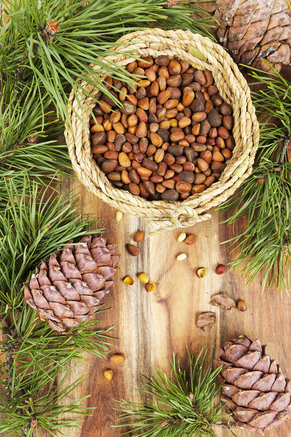 Pine nuts. Branches and cones on a wooden table royalty free stock images