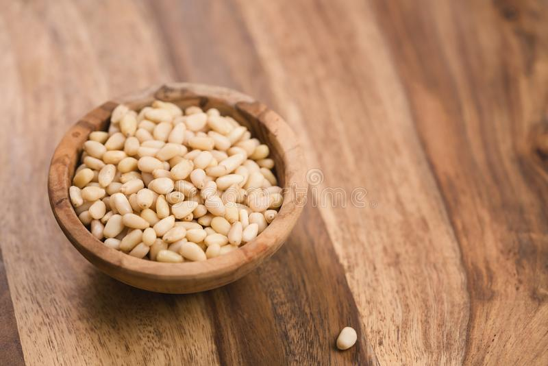 Pine nuts in wood bowl on table stock photos