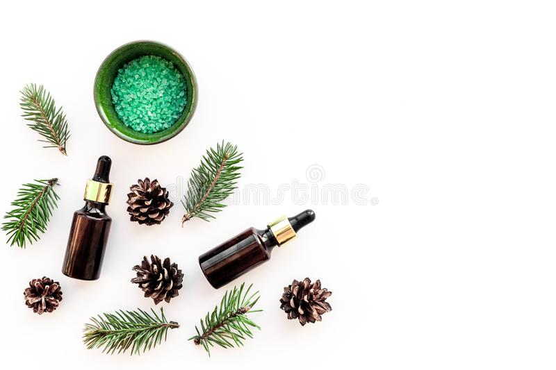 Pine spa cosmetics, products for skin care. Fir essential oil and green aromatic spa salt near branches and cones on royalty free stock photo