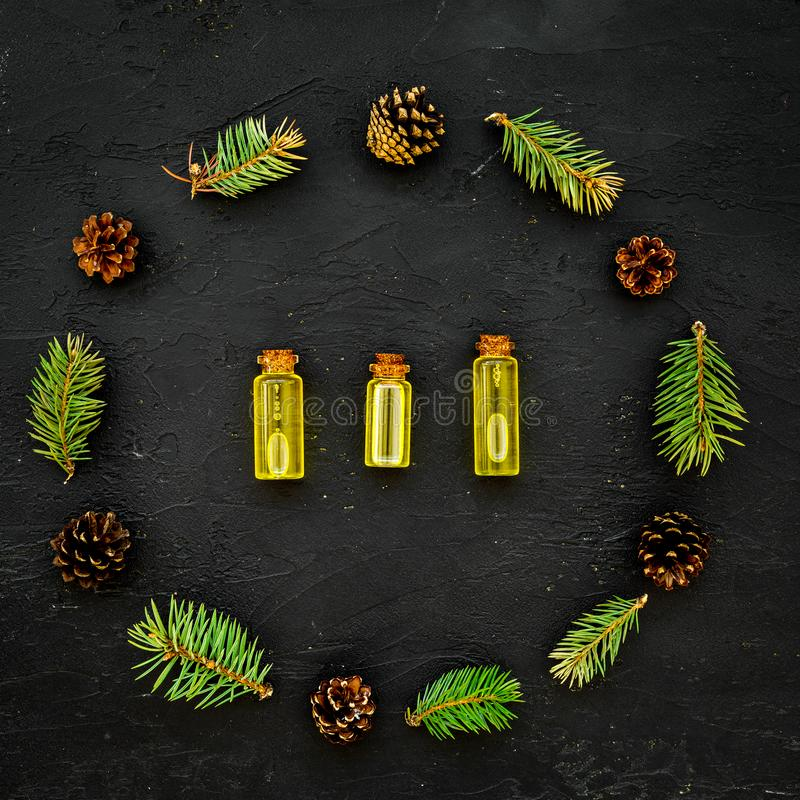 Pine spa cosmetics, products for skin care. Fir essential oil near branches and cones on dark background top view space royalty free stock image
