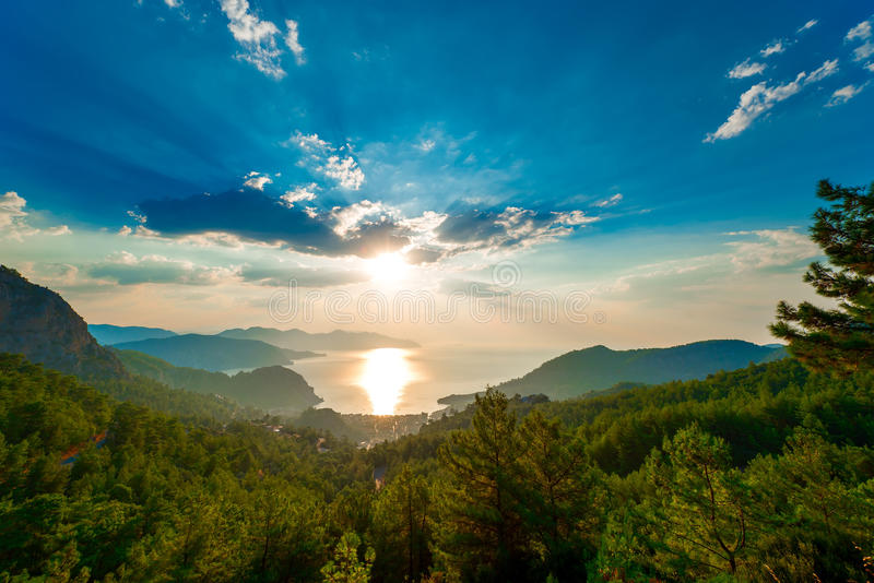 Pine trees in the mountains and the rising sun. Over the sea stock photos