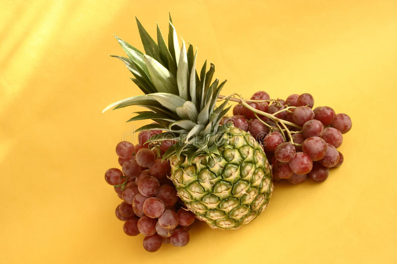 Pineapple. And grapes on yellow background stock photo