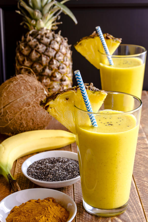 Pineapple, Banana, Coconut, Turmeric and Chia Seed Smoothies. Fresh blended fruit smoothies made with pineapple, banana, coconut, turmeric and chia seeds royalty free stock images