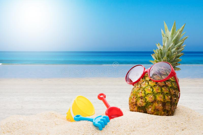 Pineapple on the beach sunbathing. Holidays and summer royalty free stock photography