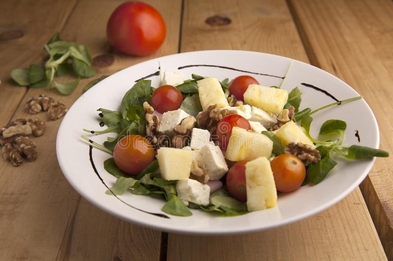 Healthy pineapple , tomato cherry , nuts and canons salad stock images