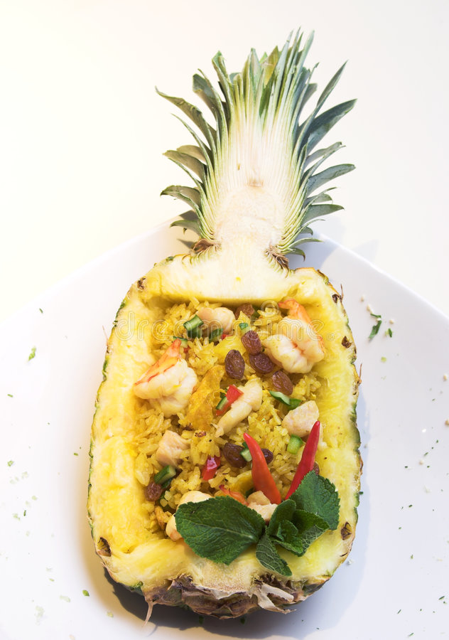 Pineapple Fried Rice. An exotic dish of fried rice inside a pineapple shell. The scattering of fine pieces around the dish is a part of the stylish of the dish stock images