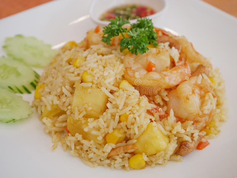 Pineapple fried rice close up. Pineapple fried rice and cucumber with fish sauce in white dish royalty free stock image