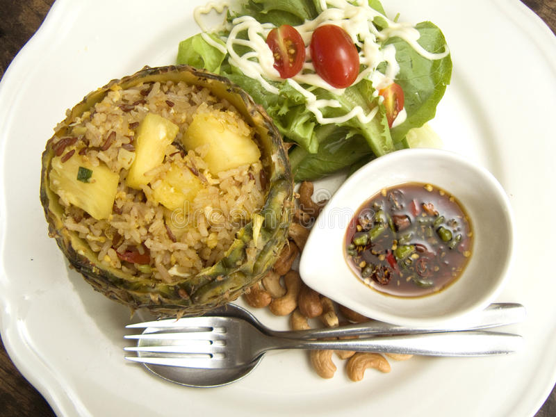 Pineapple fried rice. Delicious Asia - Asian eating Thai food. Pineapple fried rice stir with curry powder in pineapple shell served with salad, cashew nuts and royalty free stock photo