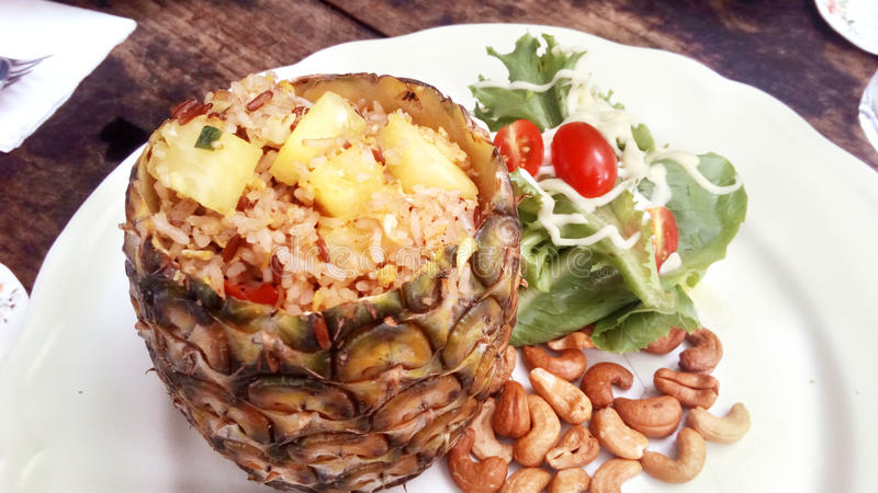 Pineapple fried rice. Delicious Asia - Asian eating Thai food. Pineapple fried rice stir with curry powder in pineapple shell served with salad, cashew nuts and royalty free stock photos