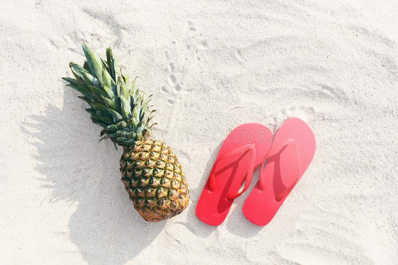 Pineapple fruit and red flip flops lying on beach white sand b. Pineapple fruit and red flip flops lying on a beach white sand background royalty free stock photography