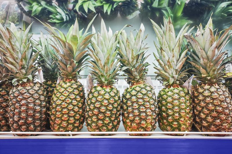 Pineapple fruits in a supermarket. Fresh pineapples on supermarket shelf.Close up royalty free stock photography