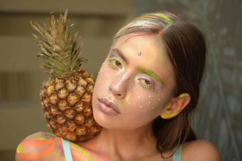Pineapple on girl shoulder on colors festival. Holi, spring royalty free stock photos