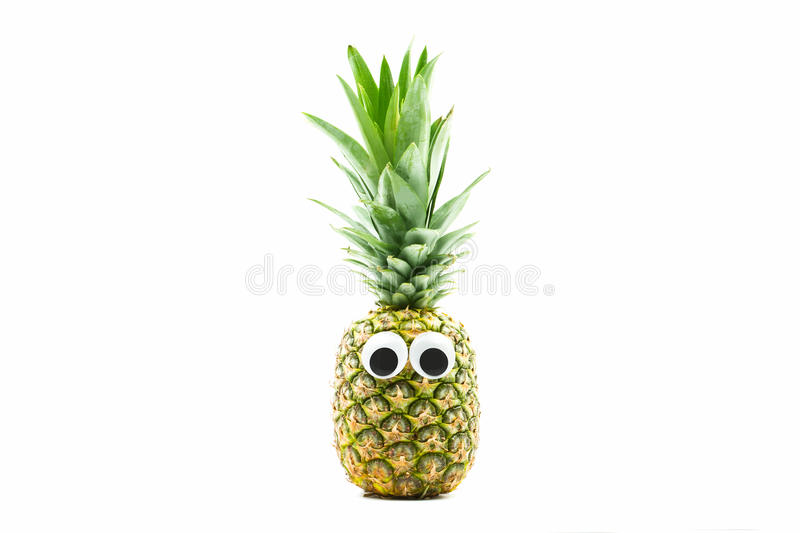 Pineapple with googly eyes on white background. Pineapple face royalty free stock photo