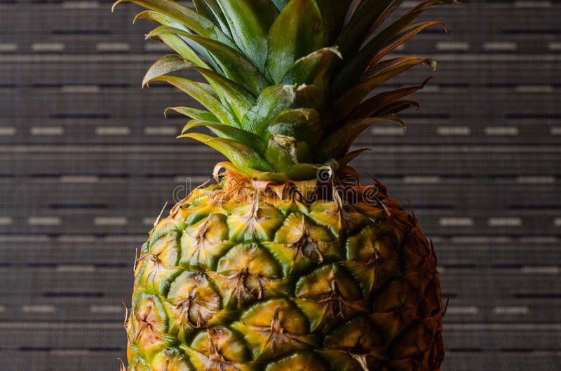 Pineapple on gray stripes background, vertical shot. Picture presents pineapple on gray stripes background, vertical shot royalty free stock images