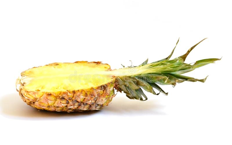 Pineapple half on white background. Pineapple slice isolated. Pineapple with leaves. Pinneaple slice. One pineapple section. Green, yellow, brown and white stock images